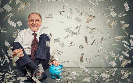 51034719 - excited happy senior man sitting on a floor with piggy bank under a money rain isolated on gray wall background. positive emotions financial success luck good economy concept